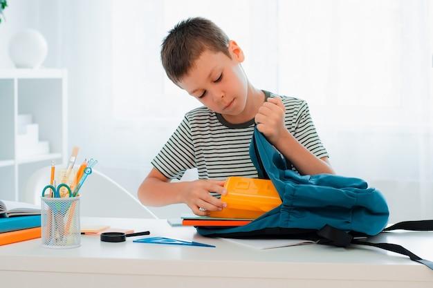 El colegial poniendo material escolar en la mochila en la mesa en el interior de la sala blanca de casa. preparación para la escuela, tarea