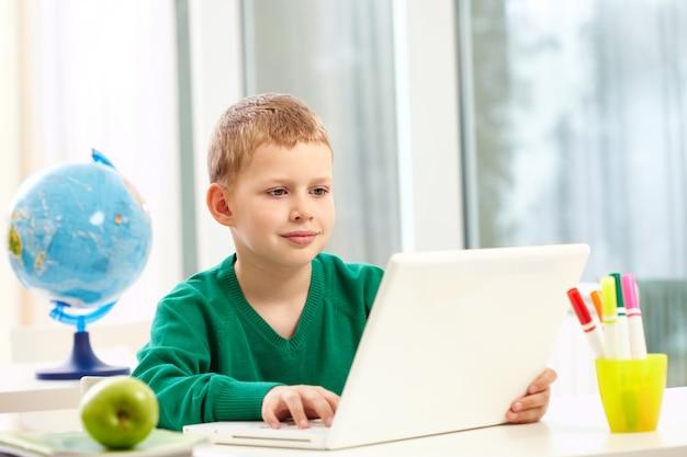 Colegial con un portátil en su pupitre