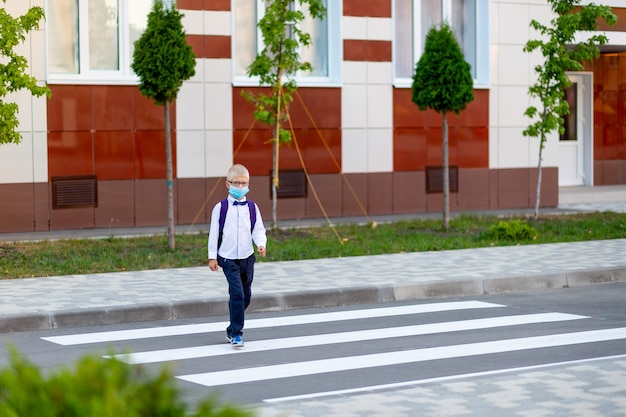 Un colegial rubio con gafas y una mochila va a la escuela en un paso de peatones