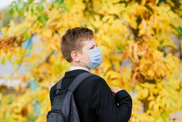 El colegial sale de la escuela con máscara protectora en la ciudad