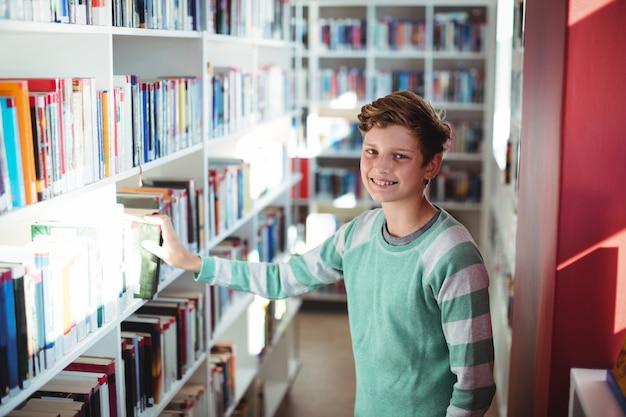 El colegial seleccionando el libro en la biblioteca