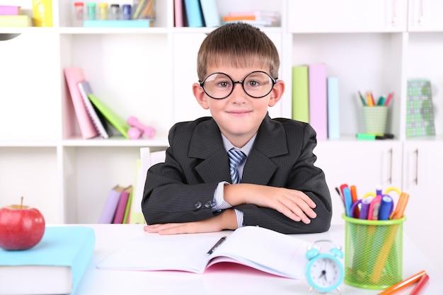 El colegial sentado a la mesa en el aula