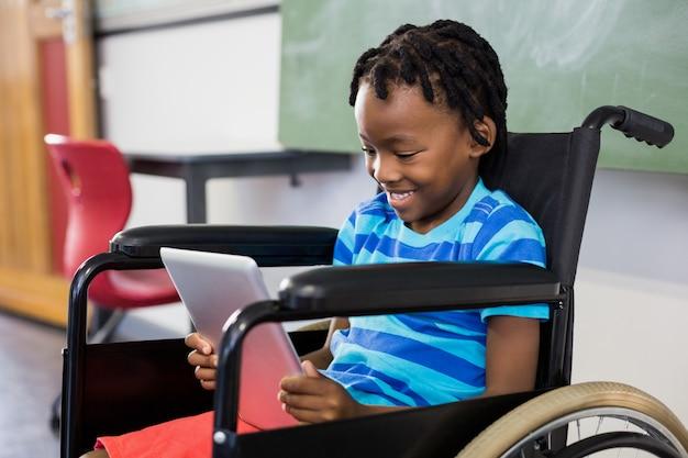 Colegial sentado en silla de ruedas y usando tableta digital