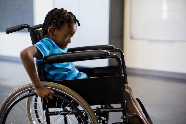 Colegial sentado en silla de ruedas