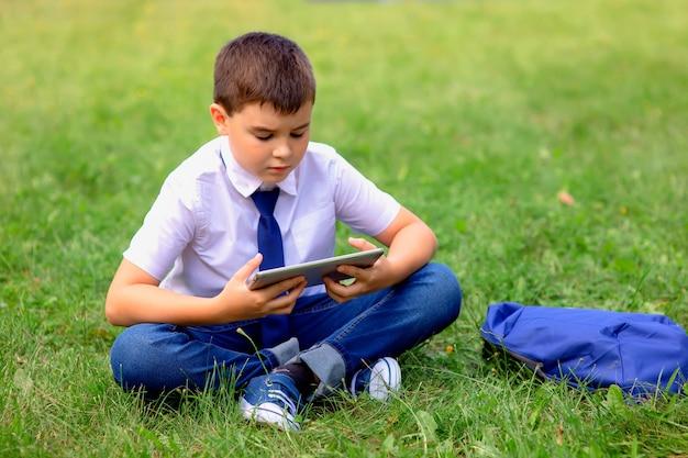 El colegial serio con una camisa blanca y corbata azul se sienta en la hierba verde contra un cielo azul con nubes blancas y mira en una tableta.