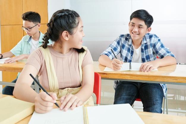 Colegial sonriente pidiendo a su compañero de clase que le ayude con la prueba