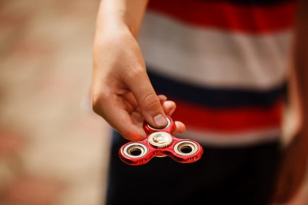 El colegial sostiene una inquietud del hilandero en sus manos. juguete de moda y popular para niños y adultos.