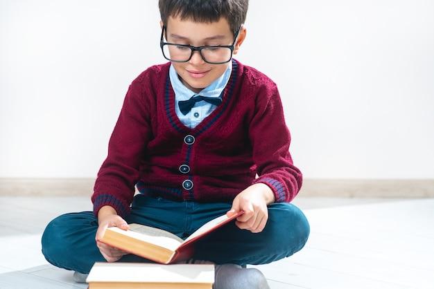 El colegial con un suéter y gafas se sienta en el suelo en posición de loto y hojea un libro.