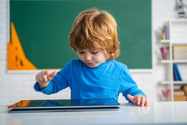 El colegial con tableta digital en el aula de la escuela