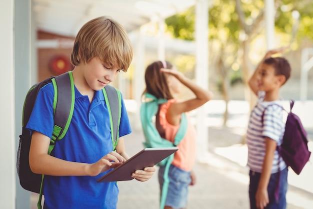 Colegial con tableta digital en el pasillo de la escuela