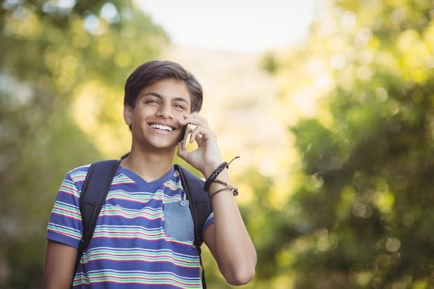 El colegial mediante teléfono móvil en el campus de la escuela
