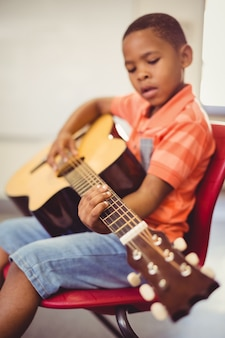 Colegial tocando la guitarra en el aula