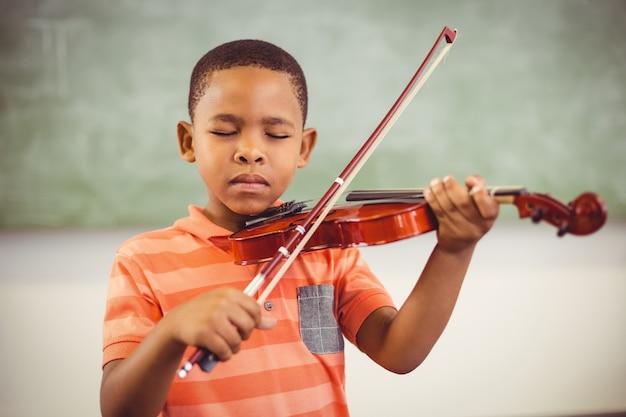 Colegial tocando el violín en el aula