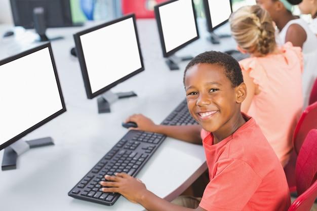 Colegial usando la computadora en el aula