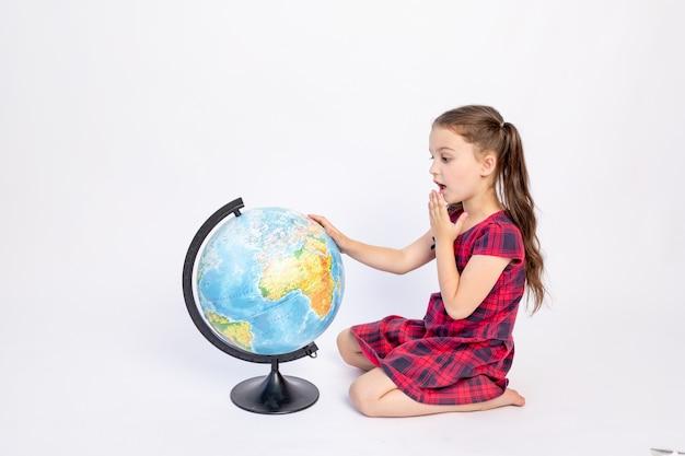 Una colegiala de 7 años sentada con un vestido rojo con un globo terráqueo sobre un fondo blanco aislado, lugar para el texto, 1 de septiembre, día del conocimiento