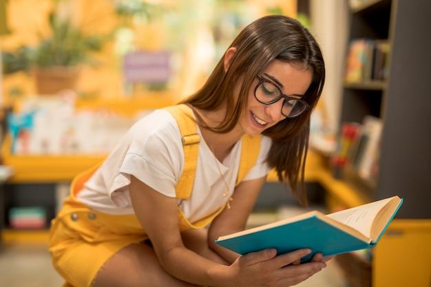 Colegiala adolescente agazapada con libro