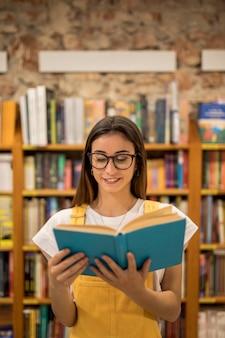 Colegiala adolescente mirando el libro de la biblioteca