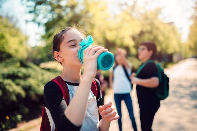 Colegiala agua potable en el patio de la escuela
