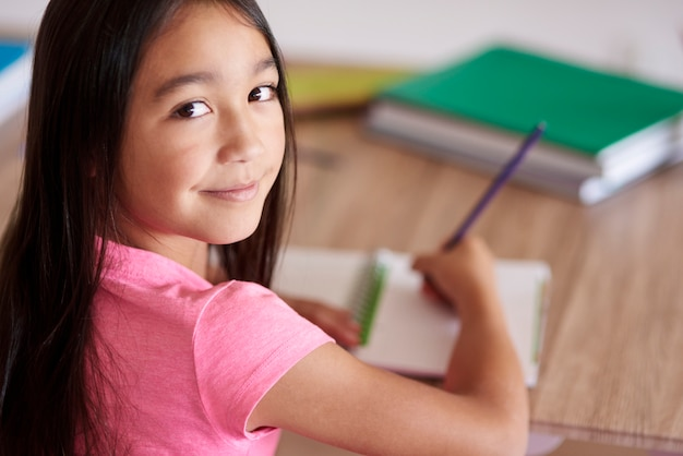 Colegiala asiática haciendo los deberes y mirando hacia atrás