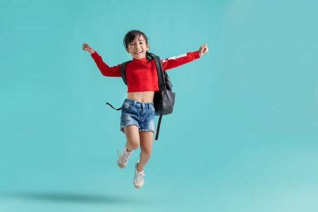 Colegiala asiática está saltando. ella es feliz.