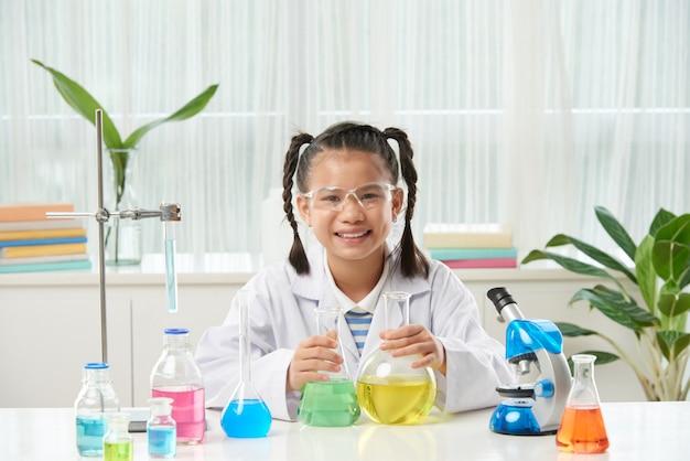 Colegiala asiática con trenzas sentado en el escritorio con microscopio y viales con líquidos coloridos