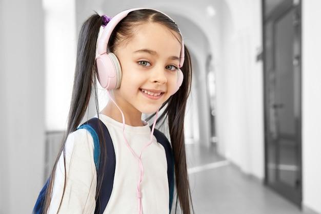 Colegiala bonita, positiva de pie en el pasillo de la escuela primaria.