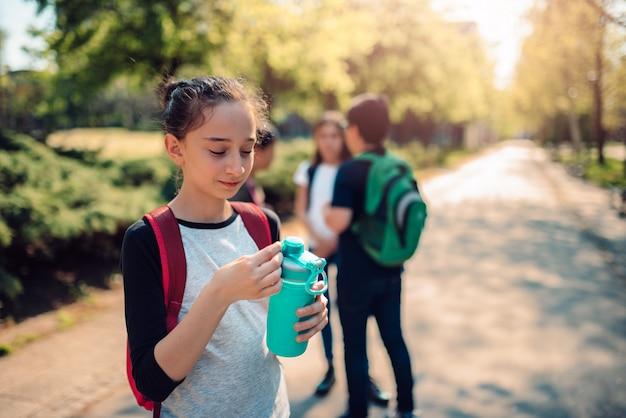 Colegiala con botella de agua en el patio de la escuela