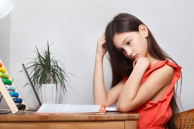 Colegiala en casa sobre educación a distancia, educación en el hogar y hacer tareas en la computadora portátil mientras está en cuarentena