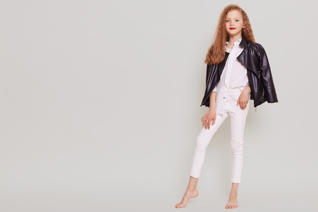 Colegiala confiada con labios brillantes de pie y mirando directamente al frente, vistiendo una elegante chaqueta de cuero