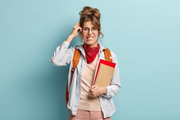 Una colegiala desconcertada sostiene un cuaderno y un diario en espiral, se muerde los labios, se rasca la cabeza mientras recuerda la información, usa un elegante pañuelo, gafas transparentes y una mochila en la espalda. estudiar el concepto