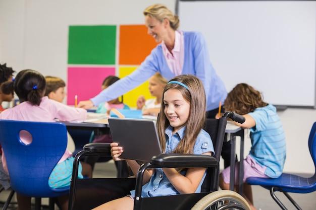 Colegiala discapacitada con tableta digital