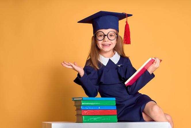 Colegiala emocionada en traje de graduación estudiando con libros de texto