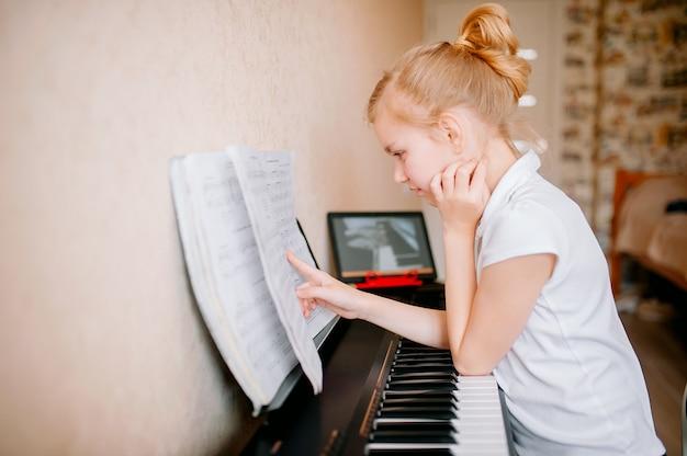 Colegiala estudiando notas y tocando el piano digital clásico mientras mira una lección en línea en una tableta y aprende a tocar el sintetizador en casa, autoaislamiento, educación en línea, distancia