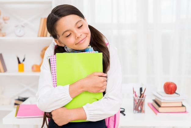 Colegiala étnica cerrando los ojos abrazando cuadernos