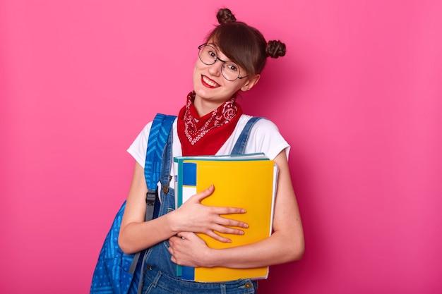 Colegiala feliz con la carpeta de papel aislada en color de rosa. muchacha sonriente que se alegra de volver a la escuela después del verano holidy. lady usa camiseta y overol, inclina la cabeza hacia el costado y sonríe