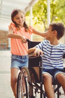 Colegiala feliz empujando a un niño en silla de ruedas
