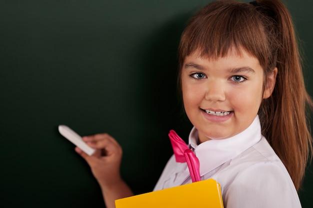 Colegiala feliz escribiendo en la pizarra