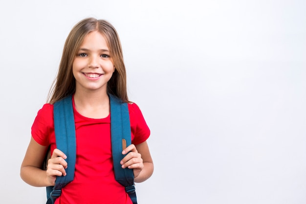 Colegiala feliz con mochila sonriendo a la cámara