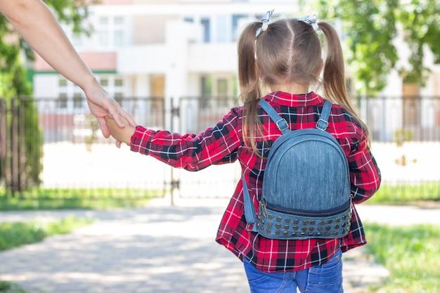 Colegiala feliz toma de la mano de las mamás y va a la escuela. con una camiseta blanca y una camisa a cuadros