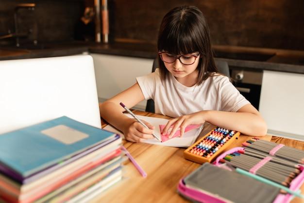 Colegiala con gafas hace la tarea en casa. aprendizaje en línea con una computadora portátil. estudia con una videollamada. educación a distancia durante la cuarentena