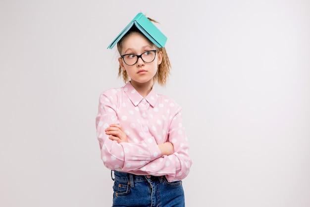 Colegiala con gafas con un libro en la cabeza