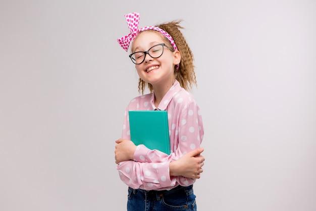 Colegiala con gafas con un libro sonriendo