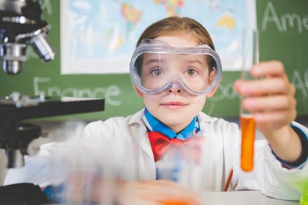 Colegiala haciendo un experimento químico en laboratorio