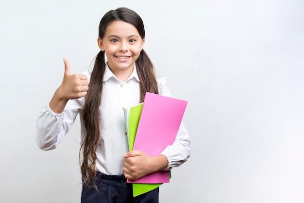 Colegiala hispana segura con cuadernos