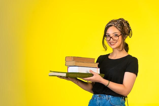 Colegiala joven en anteojos sosteniendo sus libros y sonriendo positivamente.