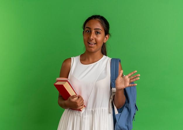 Colegiala joven complacida vistiendo bolsa trasera sosteniendo el libro con el cuaderno y extendió la mano sobre verde