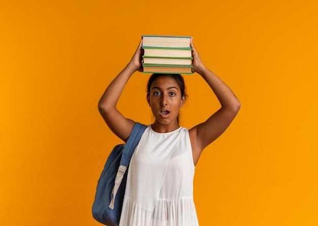 Colegiala joven sorprendida con bolsa trasera sosteniendo libros en la cabeza en naranja