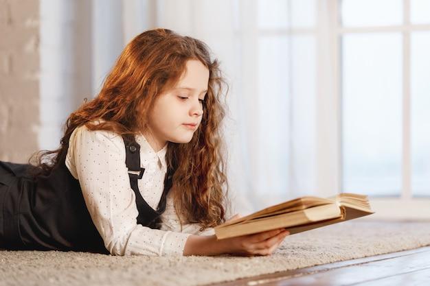 Colegiala leyendo el libro en casa.