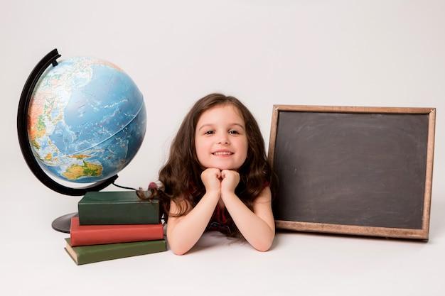 Colegiala con libros, un globo y un tablero de dibujo en blanco