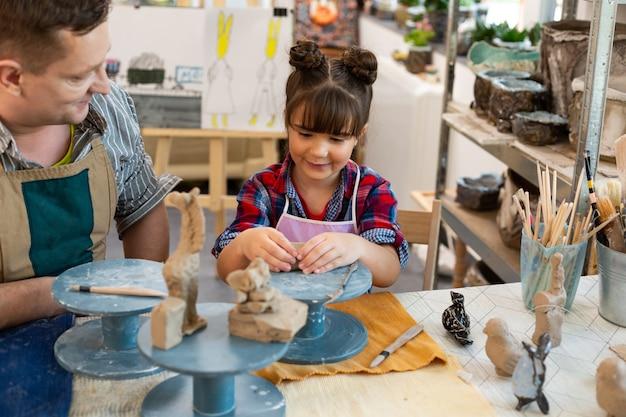 Colegiala linda alegre sonriendo mientras esculpe arcilla en la escuela de arte